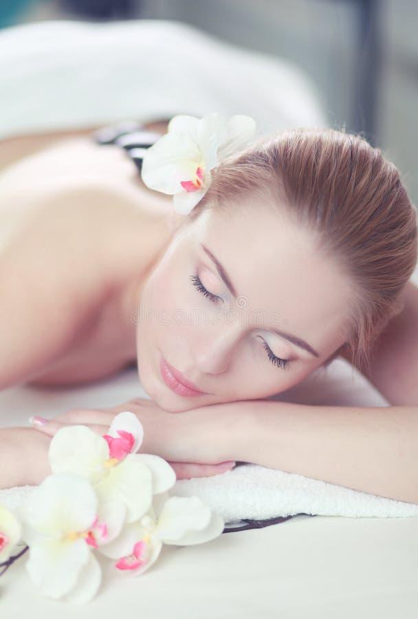 享受在一束温泉沙龙和白花的年轻女人热的岩石按摩在她的头 库存图片
