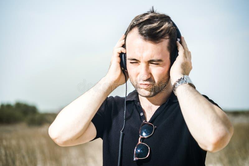 享受在他的耳机的年轻可爱的人音乐 免版税库存图片