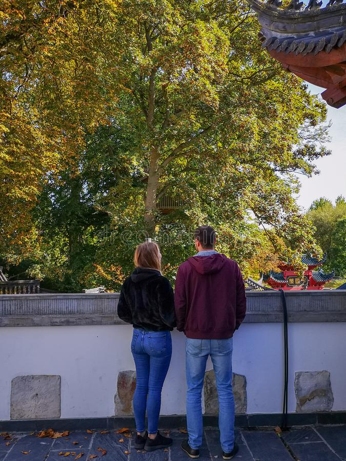 享受在传统中国庭院的年轻白种人夫妇看法在野生生物公园Pairi Daiza 免版税库存照片