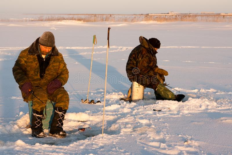 享受在冰的渔夫几天钓鱼 免版税库存照片