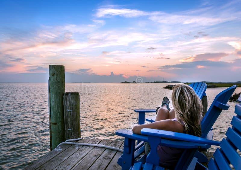 享受在切塞皮克湾码头的女性日落 免版税库存照片