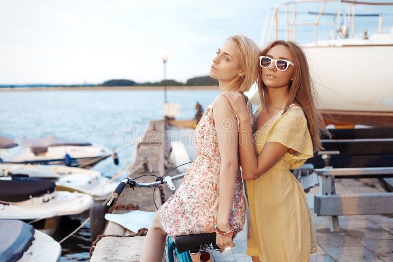 享受在口岸的两个女朋友晚上日落 库存照片