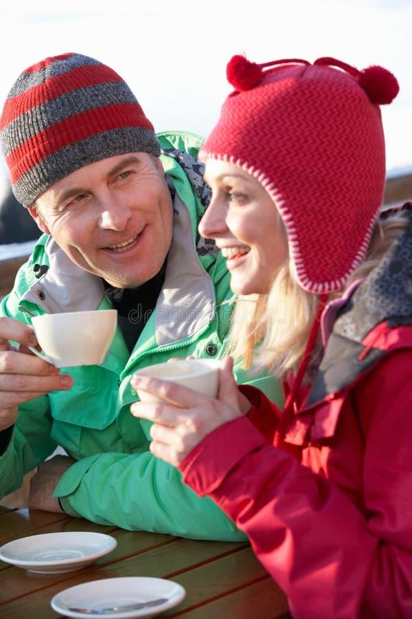 享受在咖啡馆的夫妇热饮料在滑雪胜地 免版税库存图片