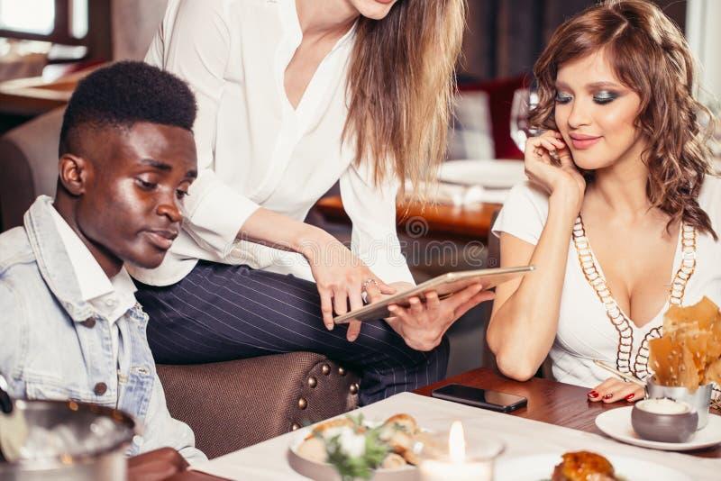 享受在咖啡馆的小组多种族朋友膳食 库存图片