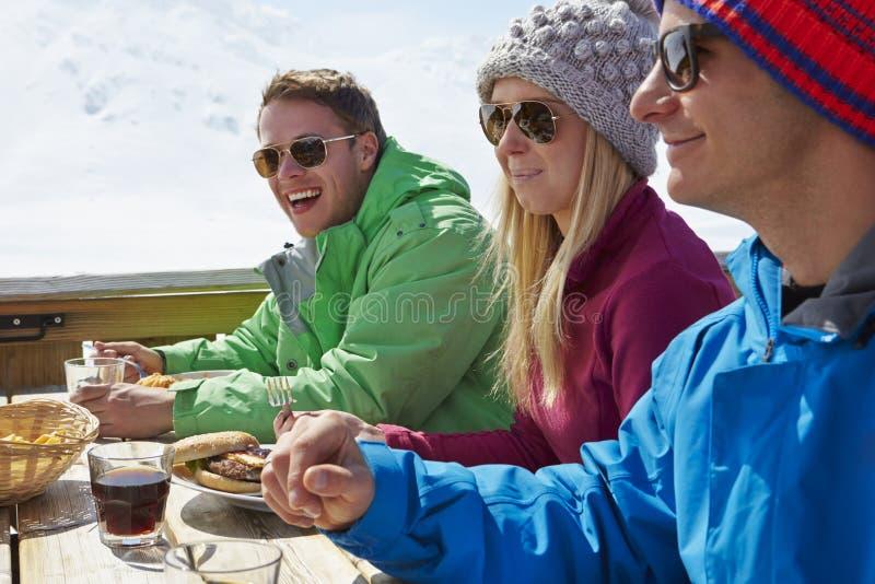 享受在咖啡馆的小组朋友膳食在滑雪胜地 免版税库存图片