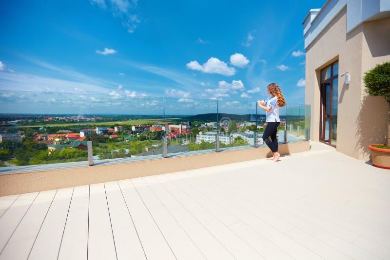 享受在城市的女孩美丽的景色站立在现代屋顶大阳台的谷的 免版税库存照片