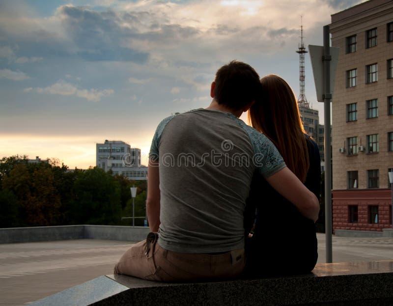 享受在城市的街道的爱夫妇日落 免版税库存照片