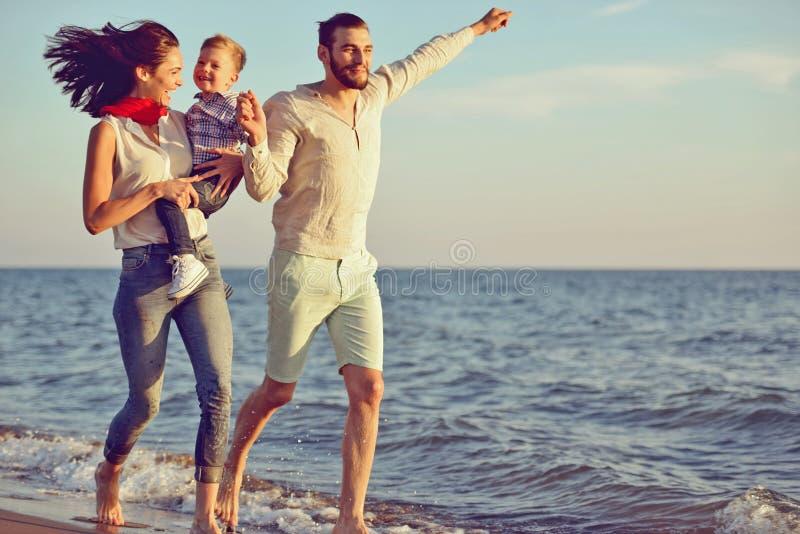享受在夏天休闲的愉快的家庭和婴孩画象日落 免版税库存图片