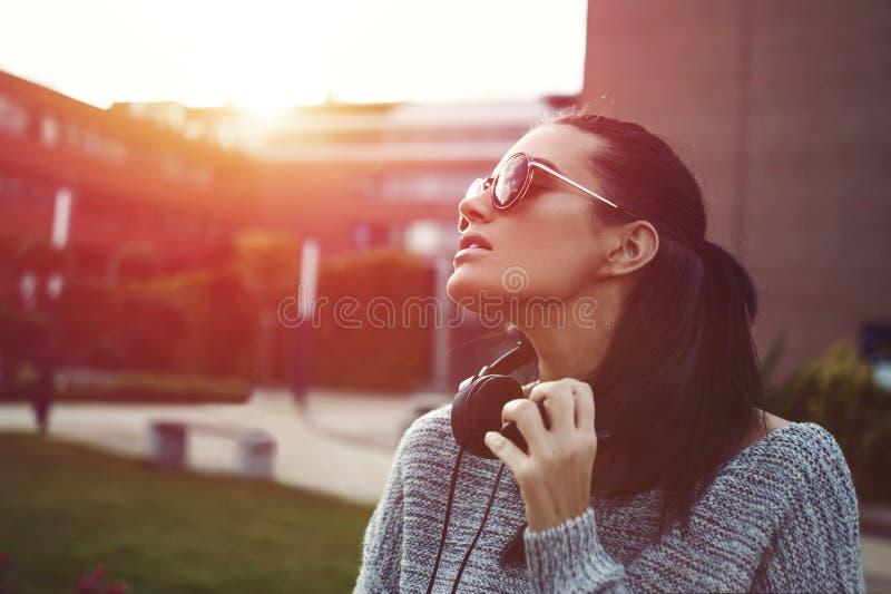 享受在太阳镜的时髦的时髦都市妇女日落 库存照片