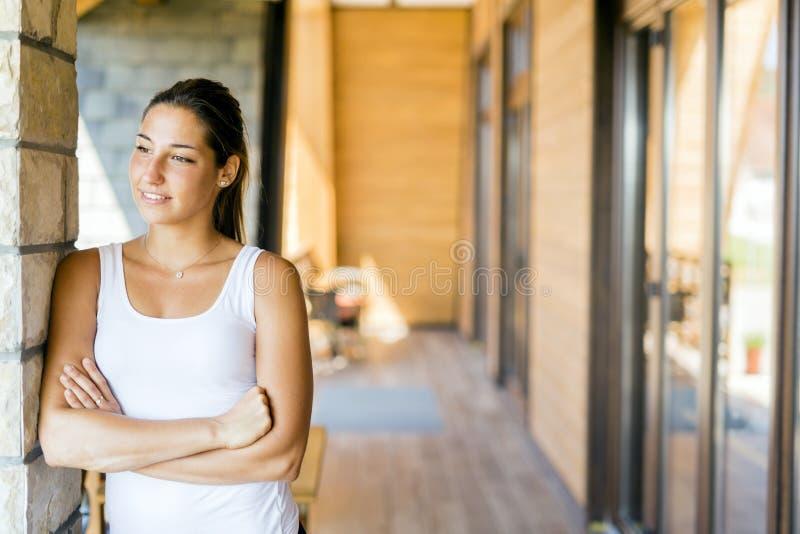 享受在她的大阳台的美丽的妇女早晨日出 图库摄影