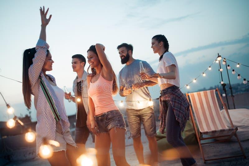 享受在屋顶大阳台的无忧无虑的小组愉快的朋友党 免版税库存照片