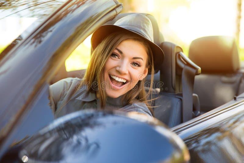 享受在敞篷车的一名年轻逗人喜爱的妇女的射击驱动爱在她的面孔的微风 免版税库存照片