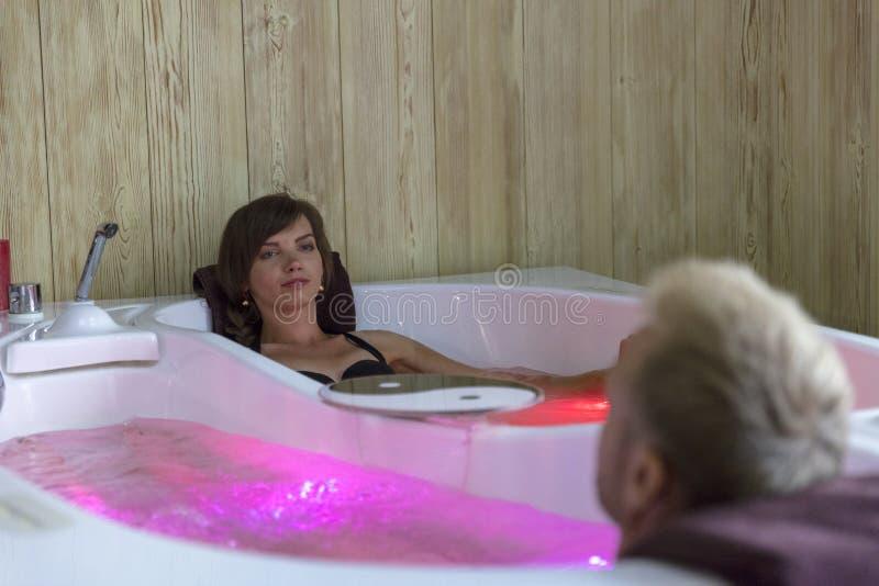 享受在极可意浴缸的年轻愉快的夫妇浴-恋人夫妇温泉水池的 图库摄影
