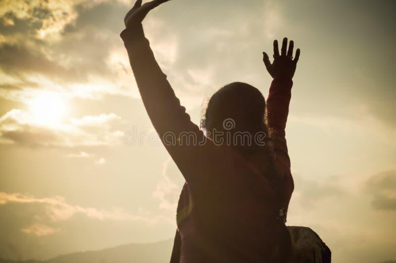 享受在橙色天空背景,培养手日落太阳的美丽的时髦的女人假日在空气关闭,后面视图 免版税库存照片
