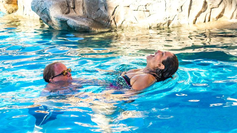 享受在水池一美好和轻松的天的夫妇 库存照片