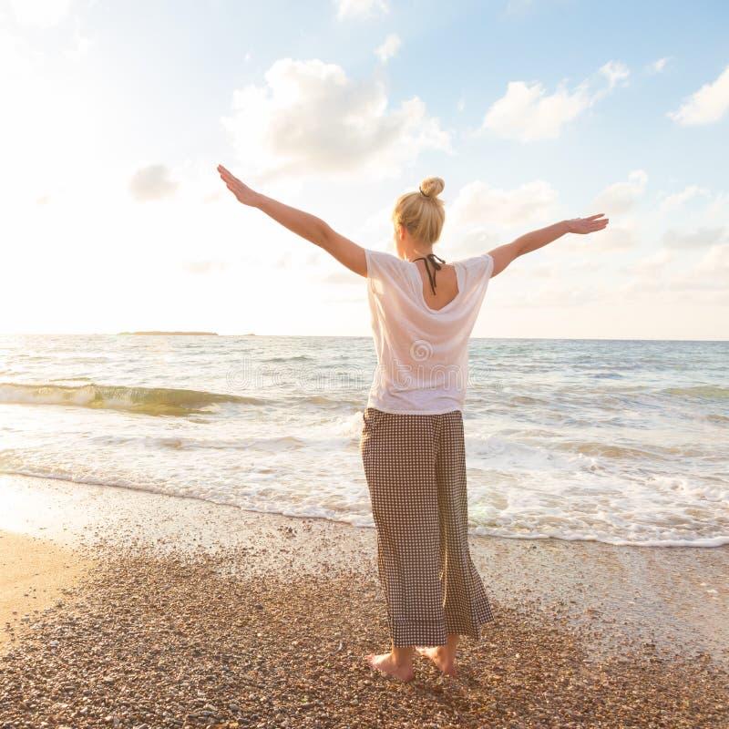享受在沙滩的自由的愉快的妇女日落 库存图片