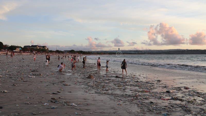 享受在海滩的人们和家庭假日在日落 免版税库存图片