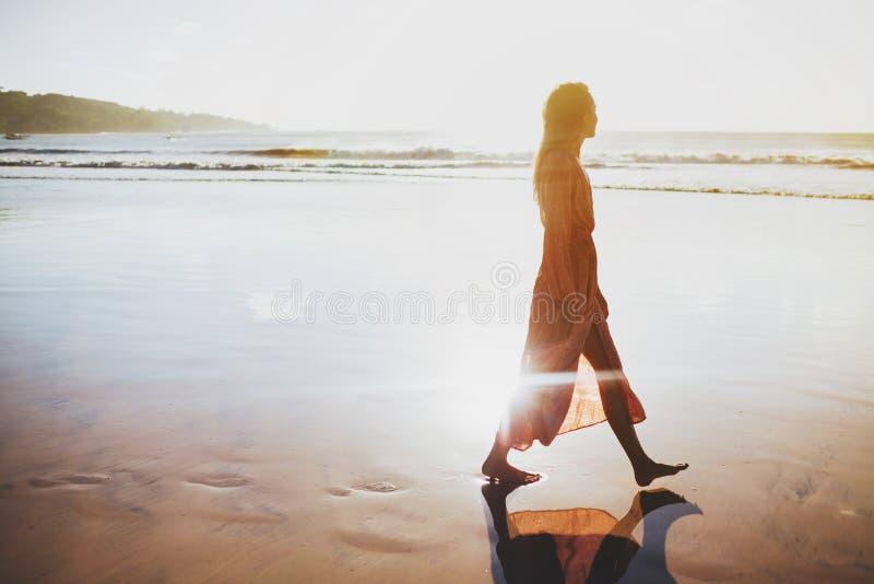 享受在海滩的妇女美好的日落 免版税库存图片