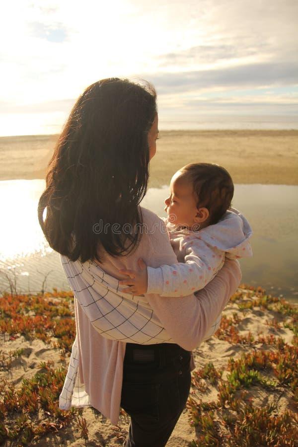享受在海滩的妈妈和婴孩时间 免版税库存照片