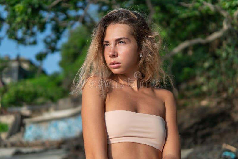 享受在海滩的年轻俏丽的女性日出 免版税库存图片