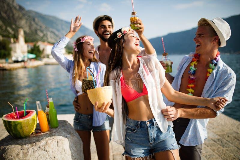 享受在海滩的年轻小组朋友夏天在日落 免版税库存照片