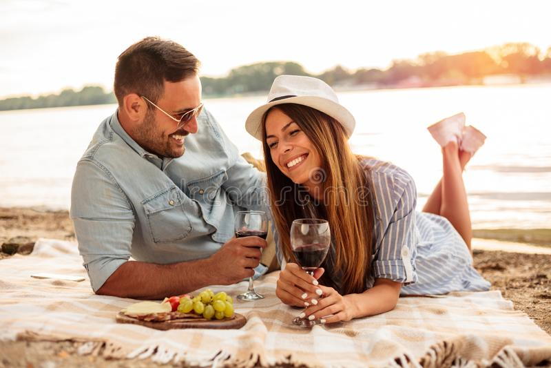 享受在海滩的美好的年轻夫妇野餐 免版税图库摄影