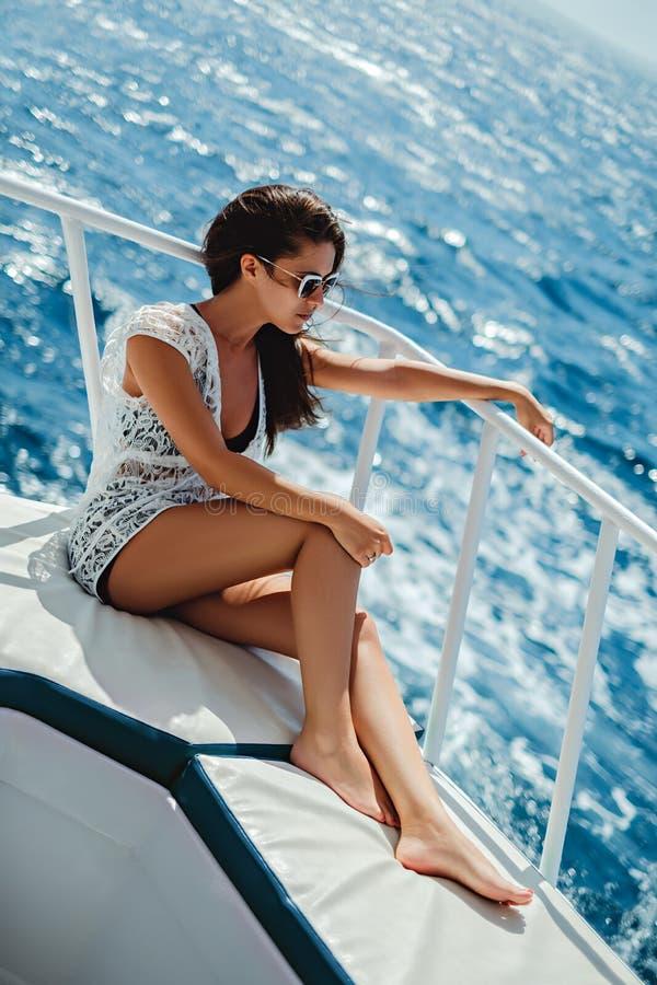 享受在海的美丽的女孩小船乘驾 免版税库存图片