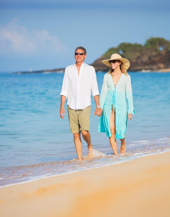 享受在海滩的中世纪夫妇步行 免版税库存照片