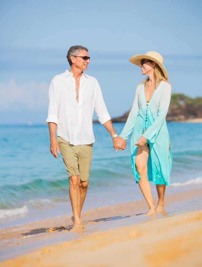 享受在海滩的中世纪夫妇步行 免版税图库摄影