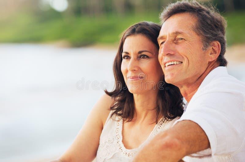 享受在海滩的成熟夫妇日落 免版税库存照片