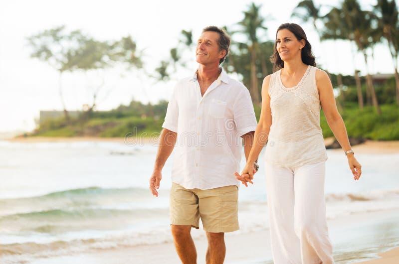 享受在海滩的成熟夫妇步行 免版税库存照片