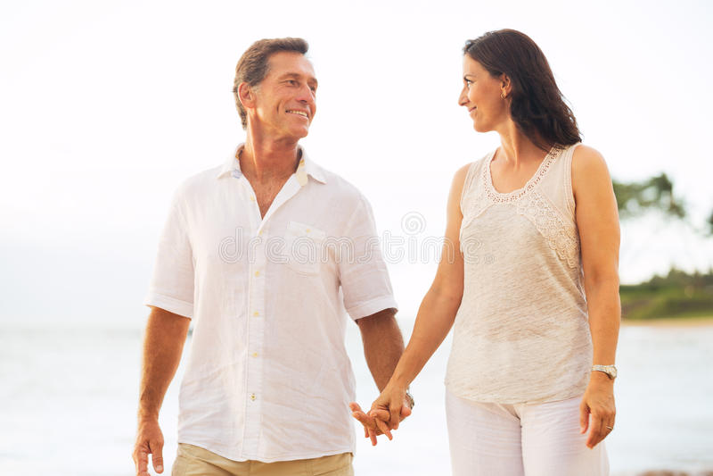 享受在海滩的成熟夫妇步行 库存图片