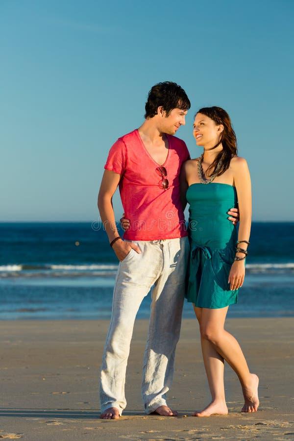 享受在海滩的男人和妇女日落 库存图片