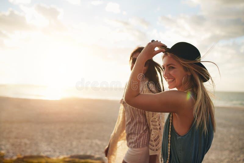 享受在海滩的美丽的朋友步行 库存照片
