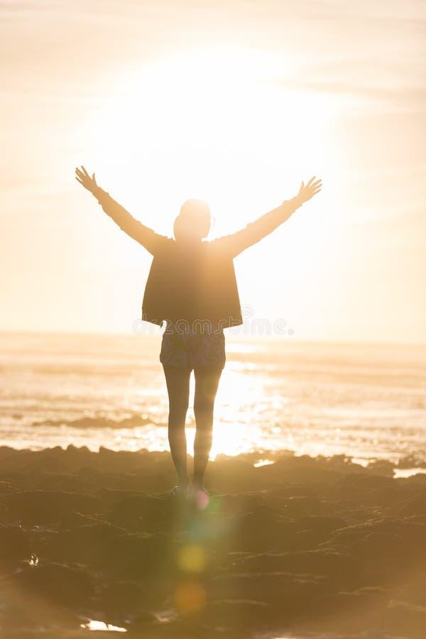 享受在海滩的自由的妇女自由在日落 免版税库存图片
