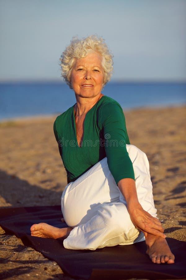 享受在海滩的资深妇女瑜伽 图库摄影