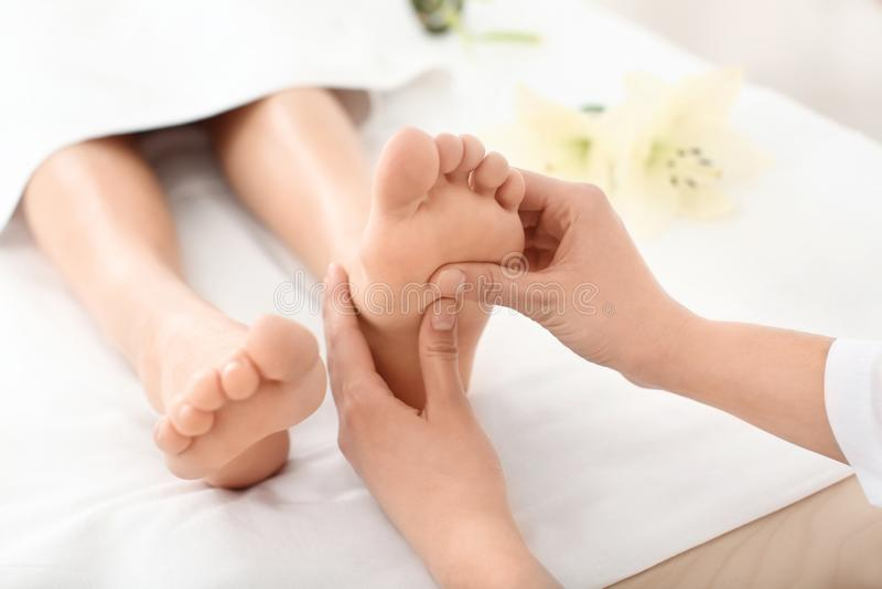享受在温泉沙龙,在腿的焦点的年轻女人脚按摩 库存图片