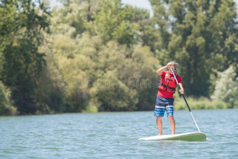 享受在湖的人乘驾有paddleboard的 库存照片