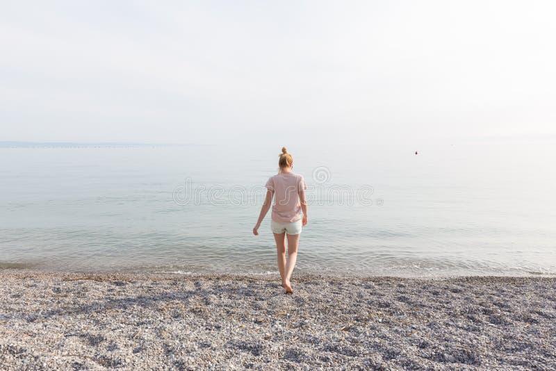 享受在白色Pabbled海滩的愉快的无忧无虑的妇女日落步行 免版税图库摄影