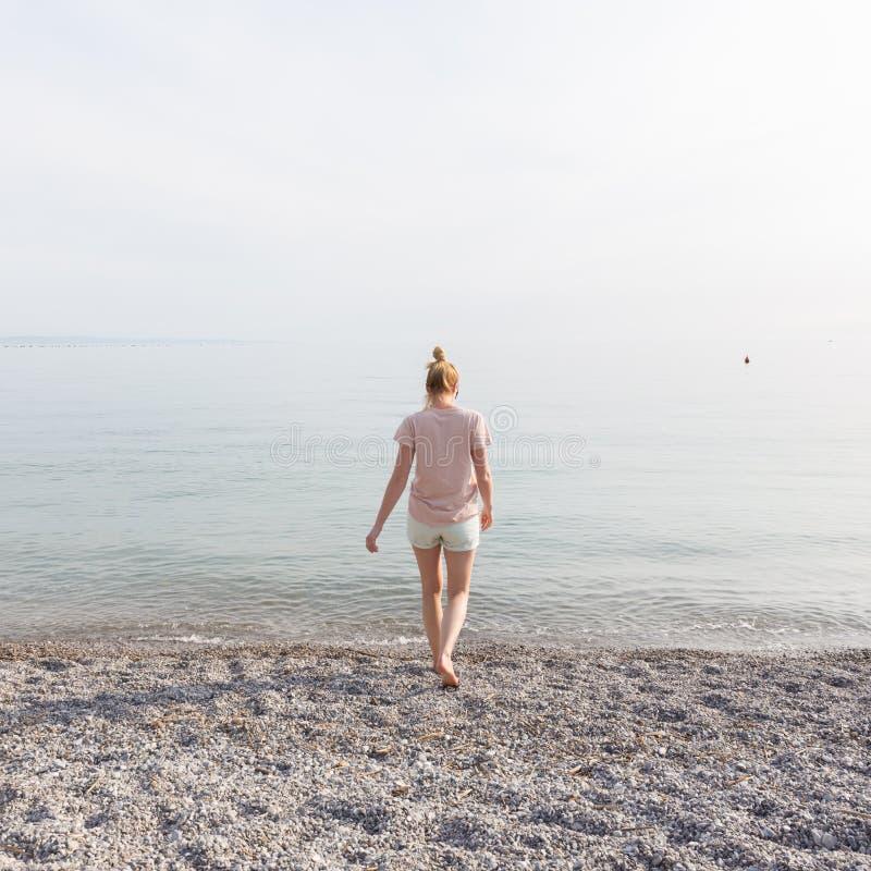 享受在白色Pabbled海滩的愉快的无忧无虑的妇女日落步行 库存照片