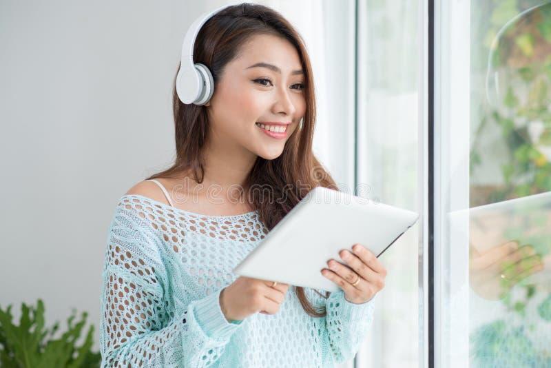 享受在窗台的看法和听到音乐的亚裔妇女 免版税库存图片