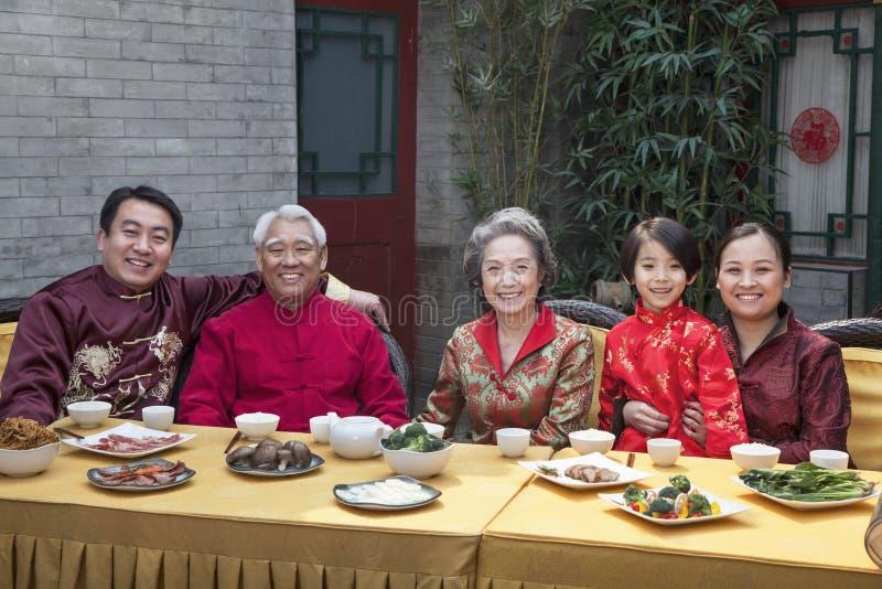 享受在繁体中文衣物的家庭画象中国膳食 库存图片