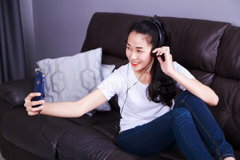 享受在耳机的妇女音乐,做与cel的selfie照片 免版税图库摄影