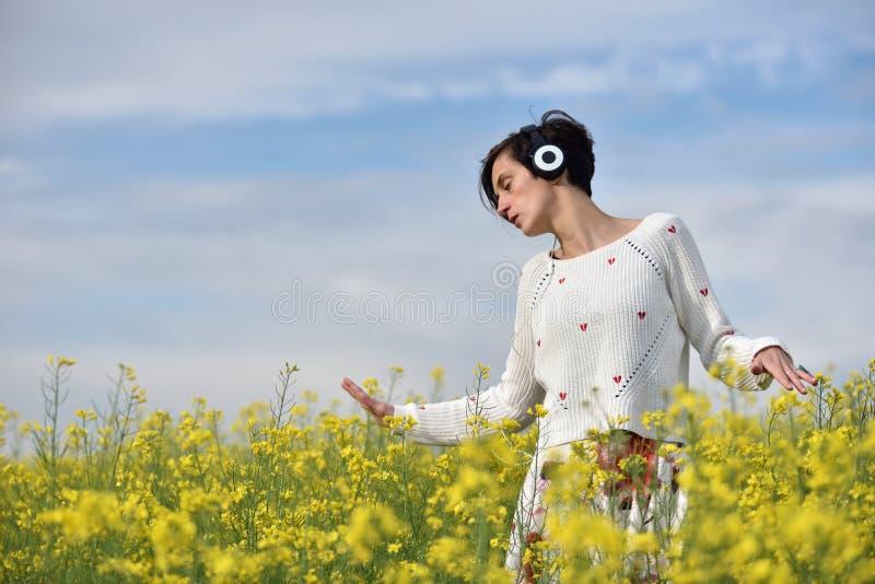 享受在耳机的少妇音乐在户外 免版税图库摄影