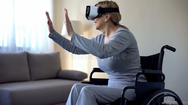 享受在耳机的老有残障的妇女虚拟现实,现代技术 库存照片