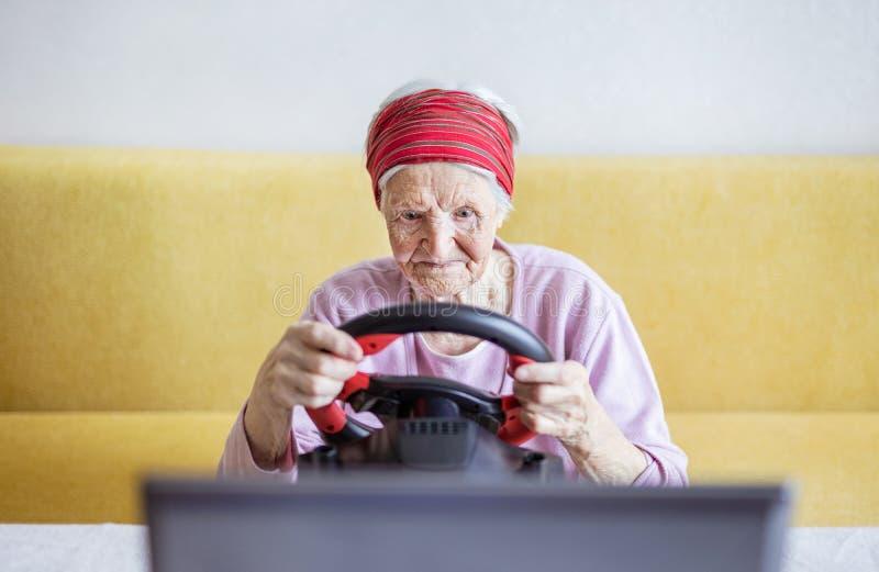 享受在膝上型计算机的资深妇女小汽车赛电子游戏,当坐长沙发时 免版税库存照片
