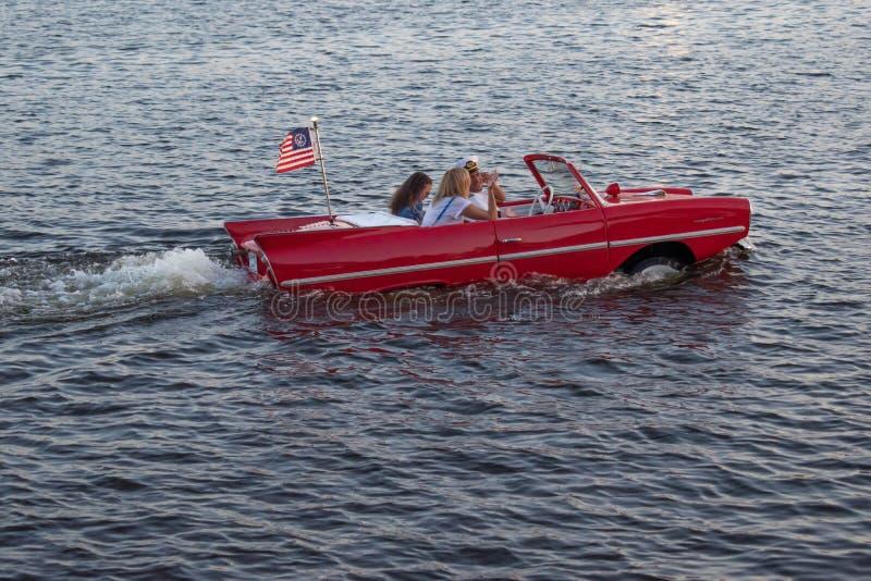 享受在葡萄酒红色amphicar的人们乘驾在迪斯尼春天1 免版税库存图片