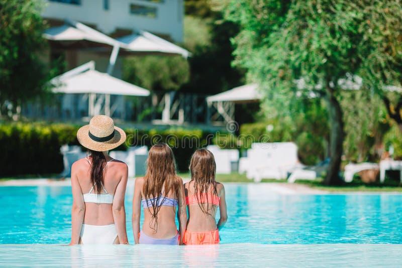 享受在豪华游泳场的母亲和两个孩子暑假 免版税库存图片