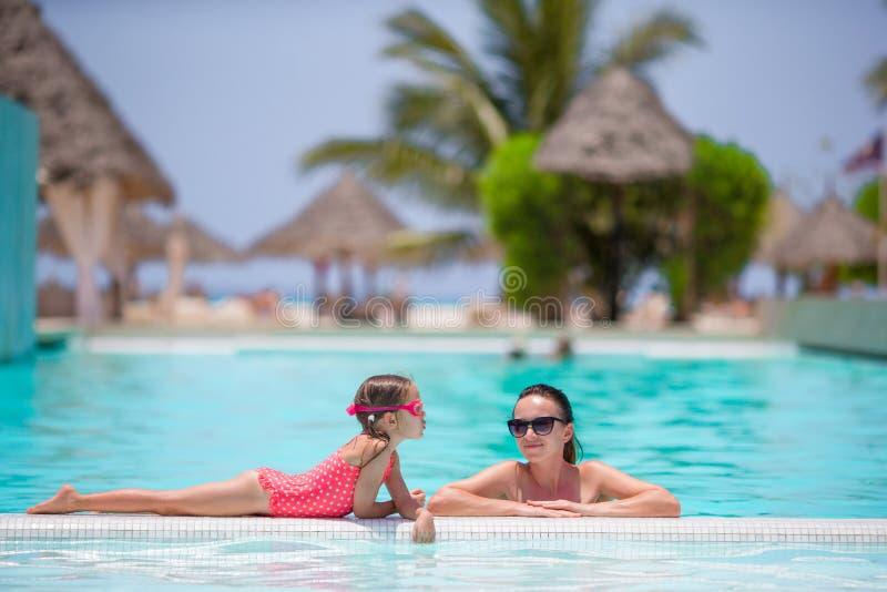 享受在豪华游泳池的母亲和孩子暑假 免版税库存图片