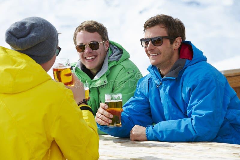 享受在酒吧的小组年轻人饮料在滑雪胜地 免版税库存照片